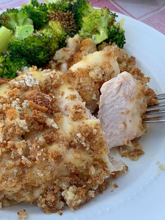 Tender and juicy bite of a pork chop on a fork by piece of casserole and broccoli