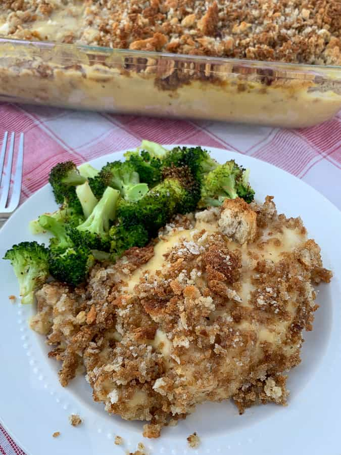 Creamy pork chop, cheese, wine and stuffing casserole on plate with broccoli by full casserole dish