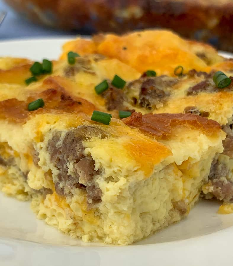Close up piece of sausage and egg breakfast casserole with chives