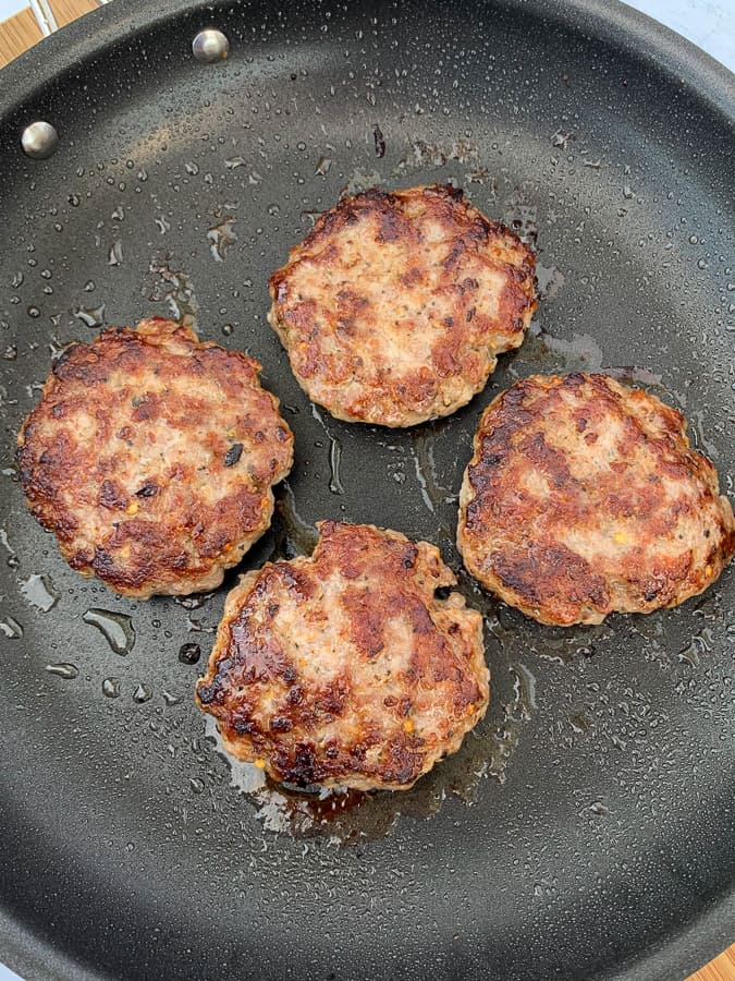 Four patties of cooked breakfast sausage with sage in a skillet