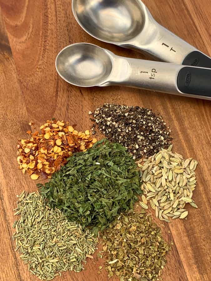 Seasonings needed to make homemade Italian sausage on a cutting board by measuring spoons