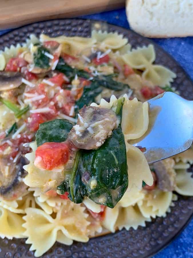 Fork full of copycat Macaroni Grill Pasta Milano over plate full