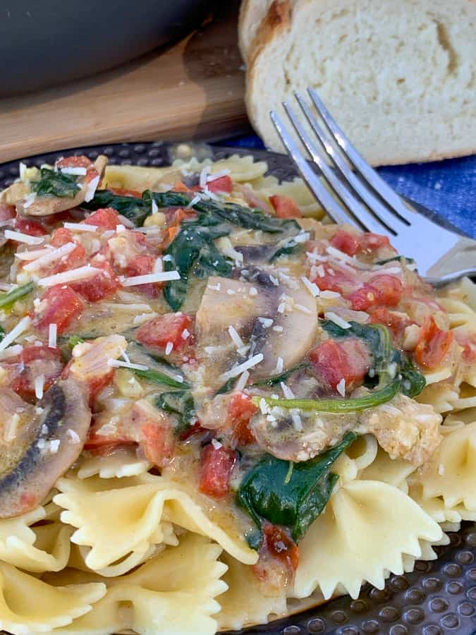 Mushrooms, spinach and tomatoes in sauce over bowtie pasta