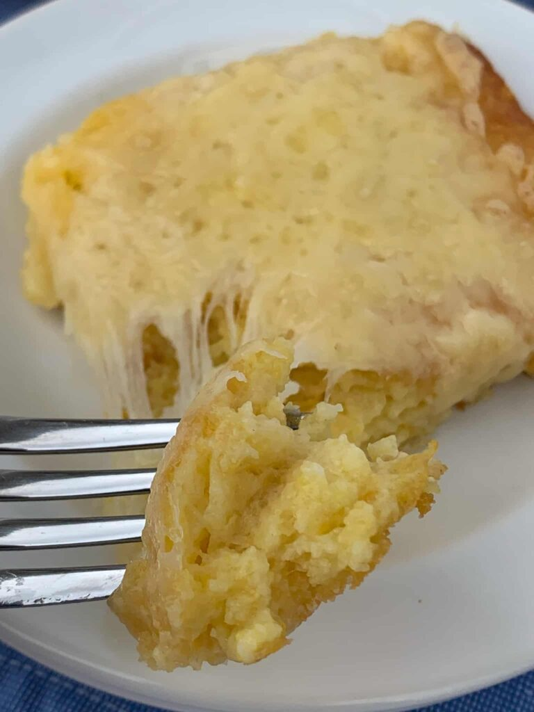 Piece of corn spoon bread on a fork with melted cheese pulling away.