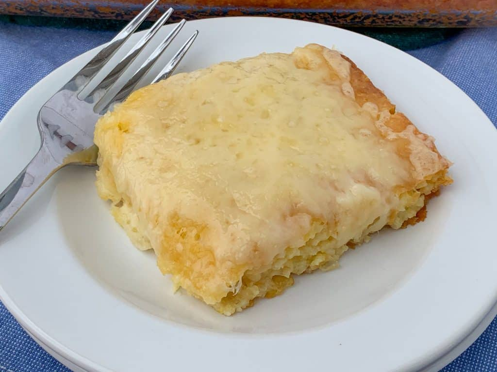 Swiss cheese melted over piece of spoon bread on a white plate with a fork