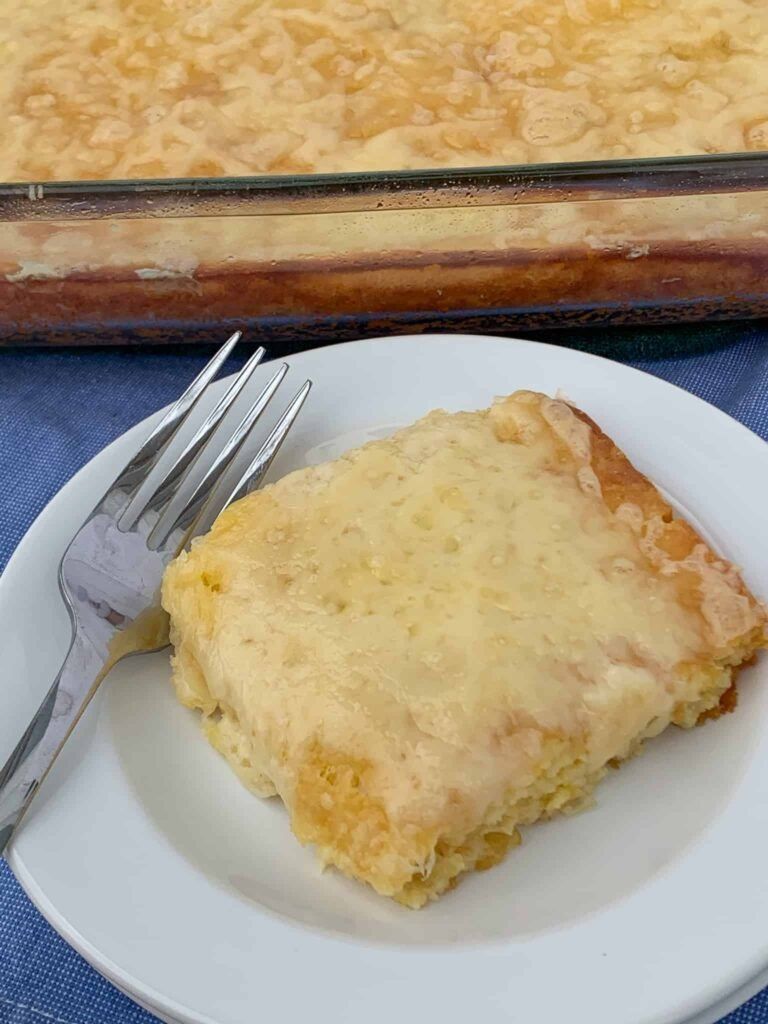 Easy sweet corn spoon bread from a Jiffy muffin mix on a plate next to large dish