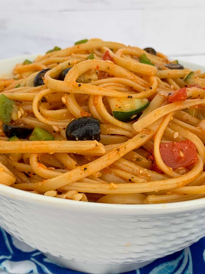 White bowl heaped with cold linguine pasta salad with chopped vegetables