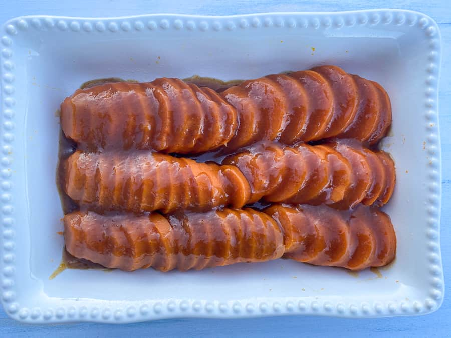 Glaze poured over sliced sweet potatoes in 9x13 dish