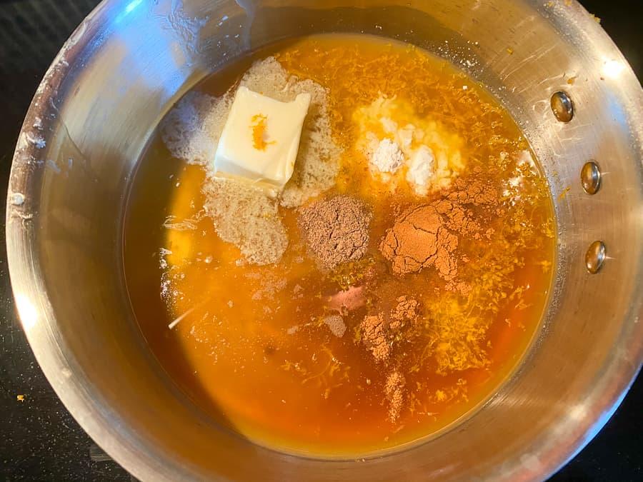 Honey, brown sugar and citrus ingredients in sauce pan to make sweet potato glaze