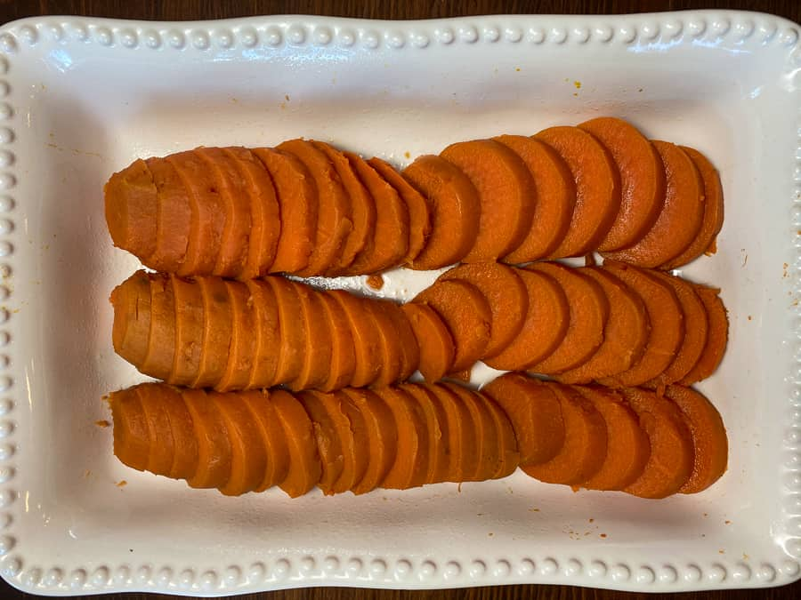 Boiled, peeled and sliced sweet potatoes lined up in a baking dish