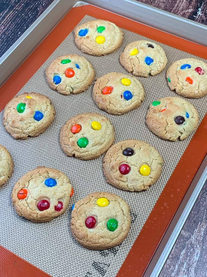 Baking sheet with a liner and M&M cookies that are a little overdone