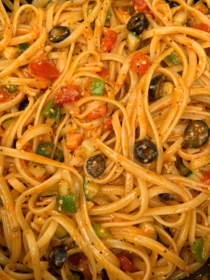 Supreme salad seasoning and Italian dressing on linguine pasta salad with tomatoes, olives, peppers and onions