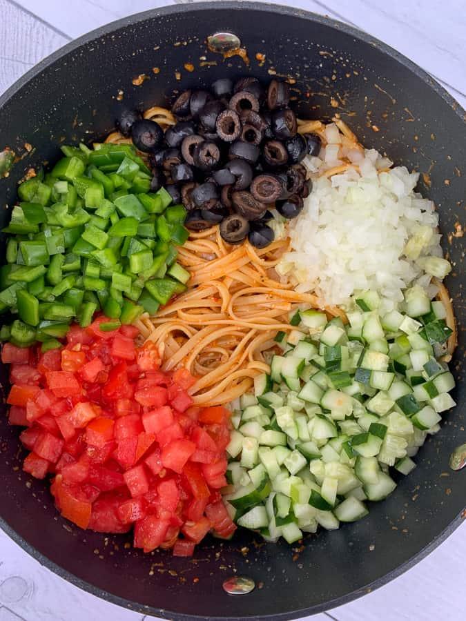 Ingredients and vegetables for pasta salad on top of seasoned linguine