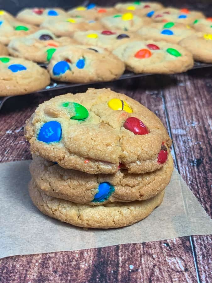 Stack of M&M cookies in front of cooling rack with cookies