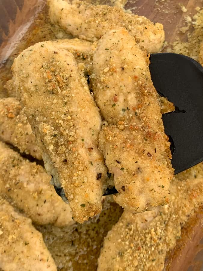 Chicken tenders with a light coating of parmesan cheese and bread crumbs on a spatula