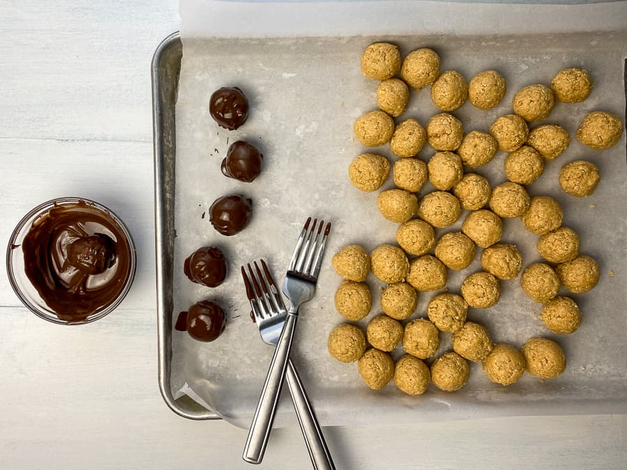 Dipping peanut butter balls into dark melted chocolate