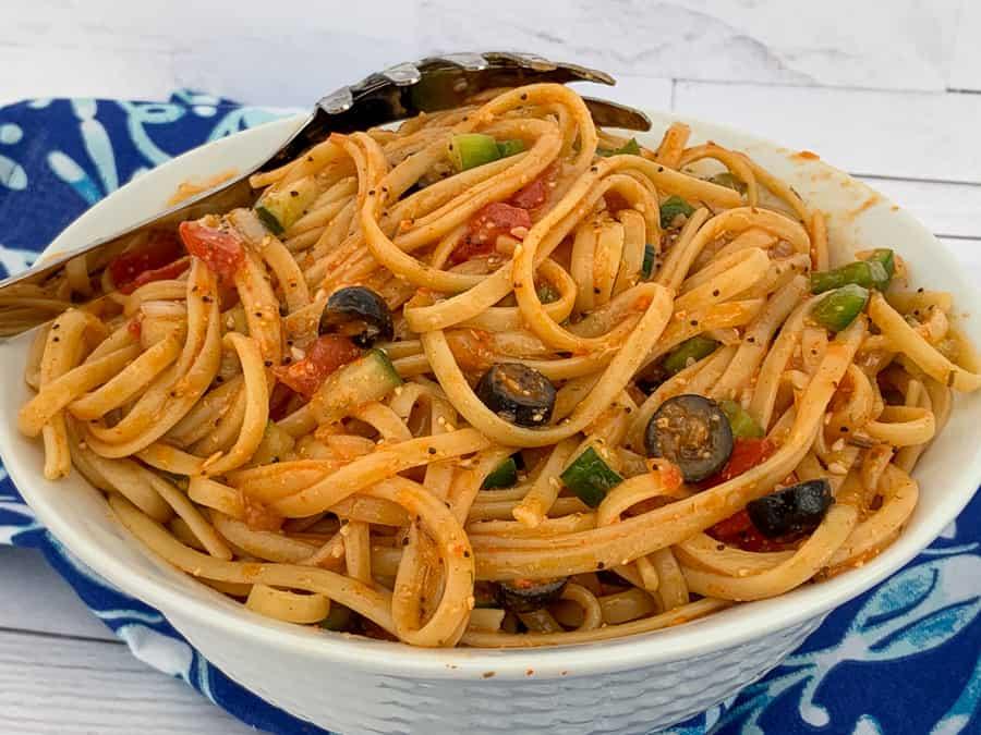 Bowl full of linguine pasta salad seasoned with salad supreme linguine salad