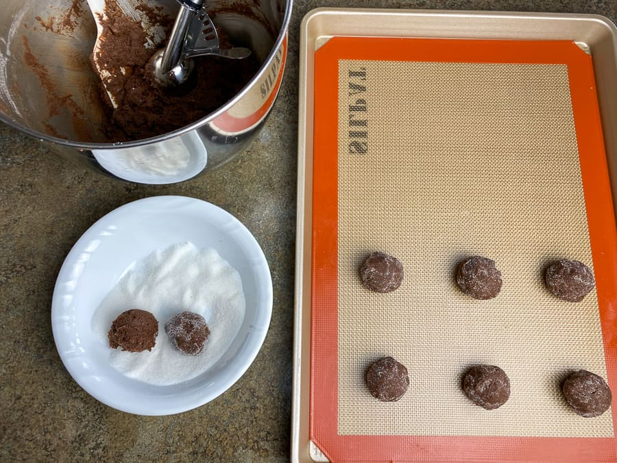 Set-up to roll balls of chocolate cookie dough in sugar and place on baking sheet