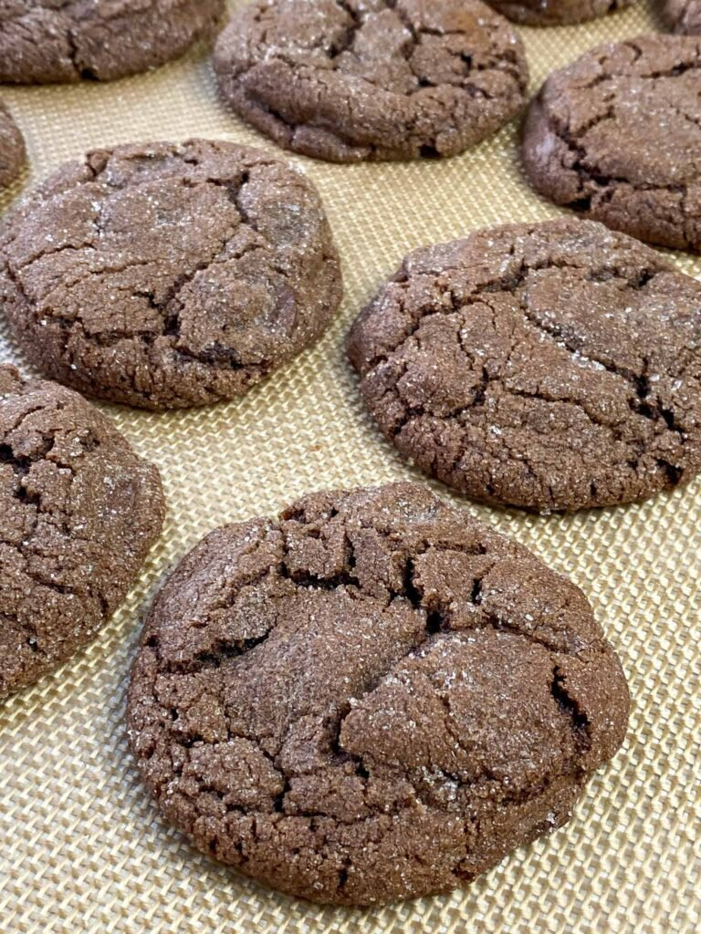 Sugar coated triple chocolate cookies on a lined baking sheet