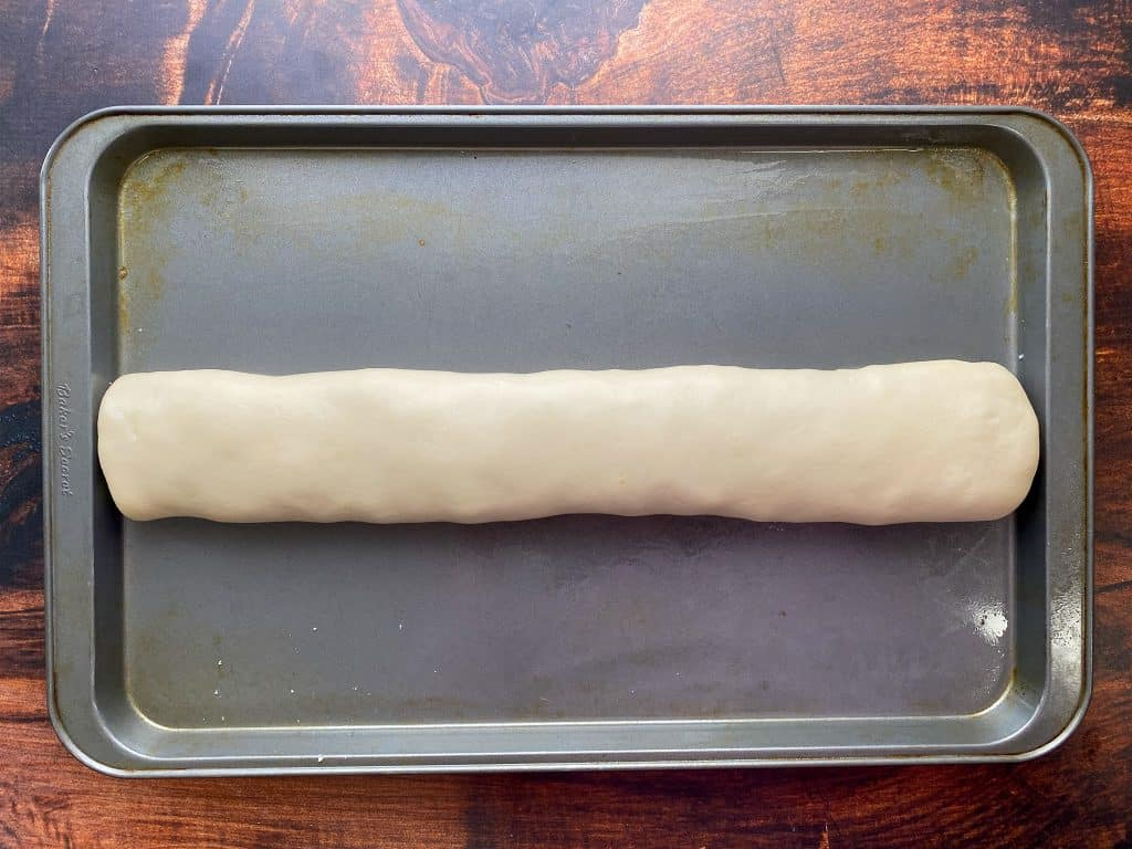 Folded and rolled stromboli from frozen bread dough on a baking sheet ready to bake