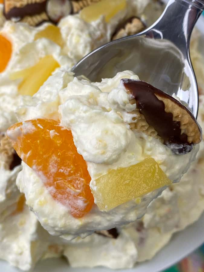 Spoonful of mandarin oranges and pineapple in fruit salad with cookie pieces.