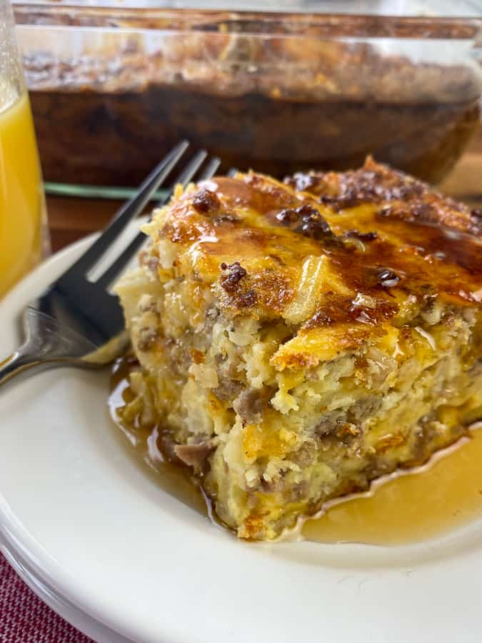 Thick piece of breakfast casserole with sausage and potatoes with syrup and fork on a white plate