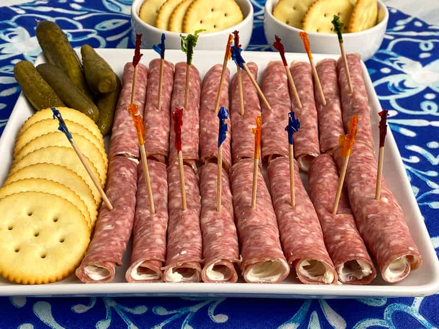 Rows of keto salami rolls with toothpicks on bright blue napkin