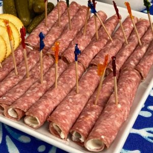 Salami roll-ups with party toothpicks on white plate