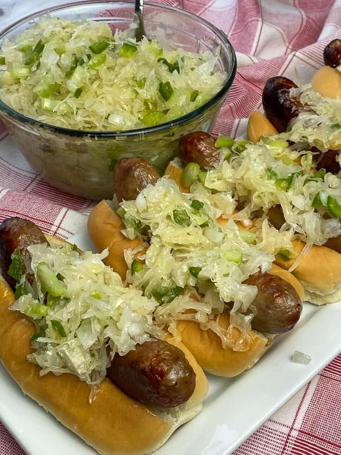 Sauerkraut salad topping on sausages next to bowl of cold sauerkraut salad