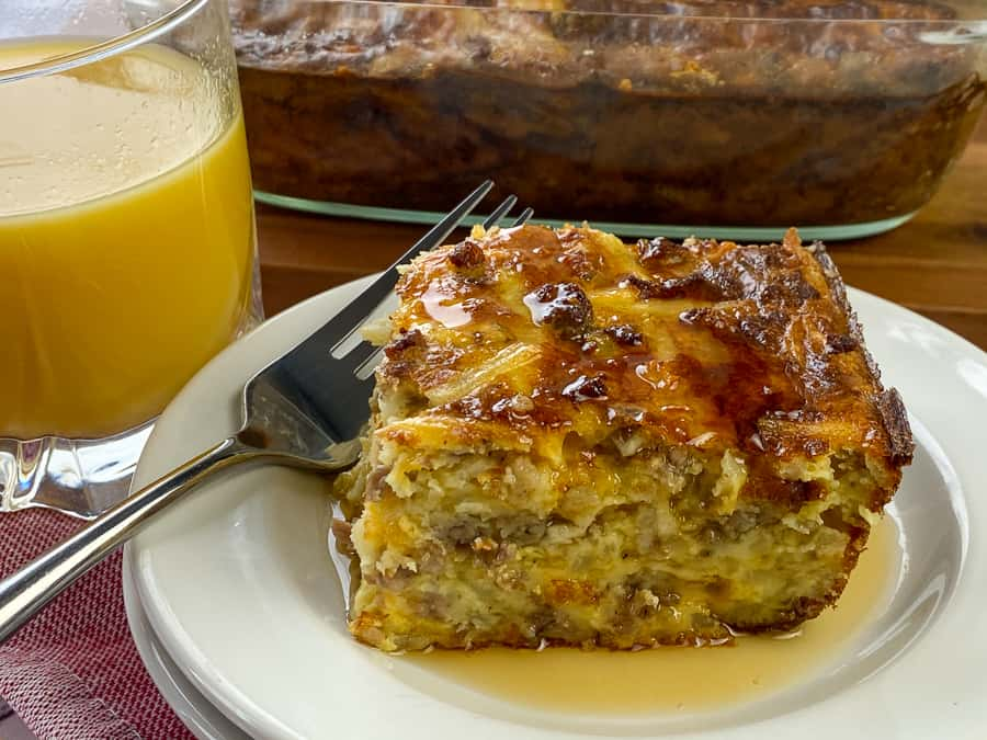 Maple syrup drizzled over sausage and hash brown casserole next to glass of orange juice and baking dish