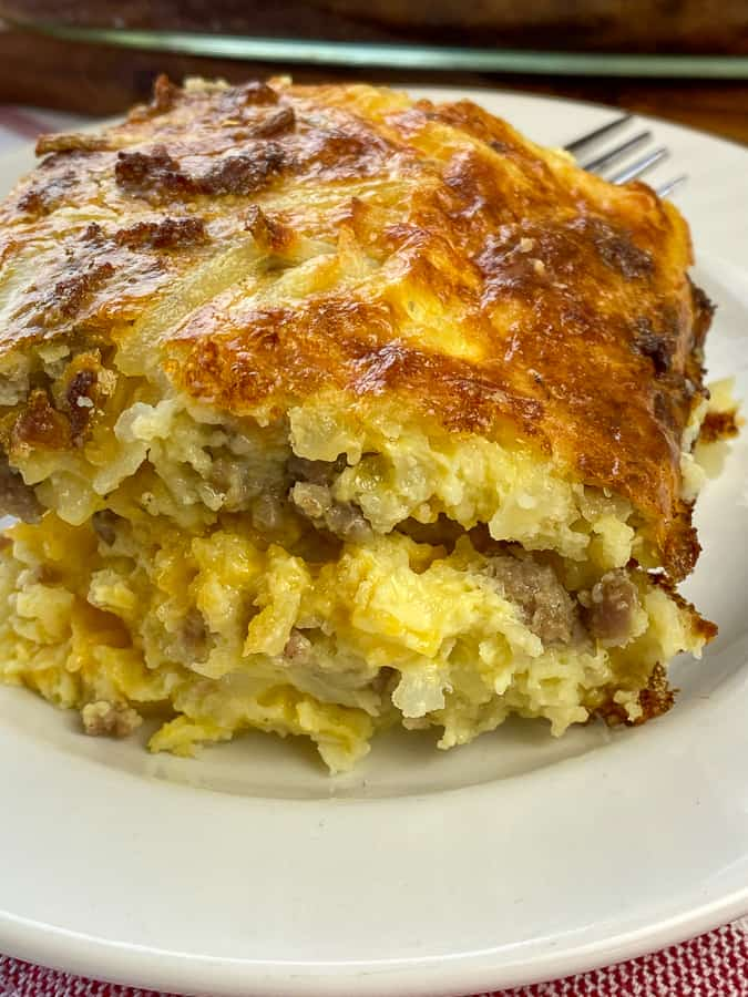 Piece of sausage hash brown casserole on a white plate