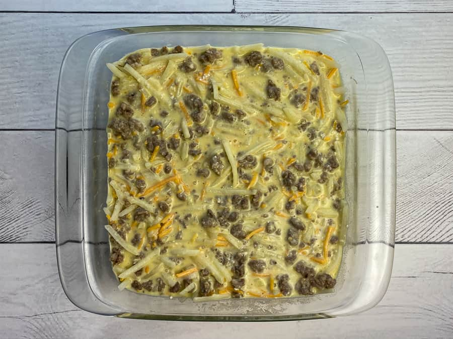 Sausage and potatoes in egg, milk, cheese and Bisquick mix in baking dish