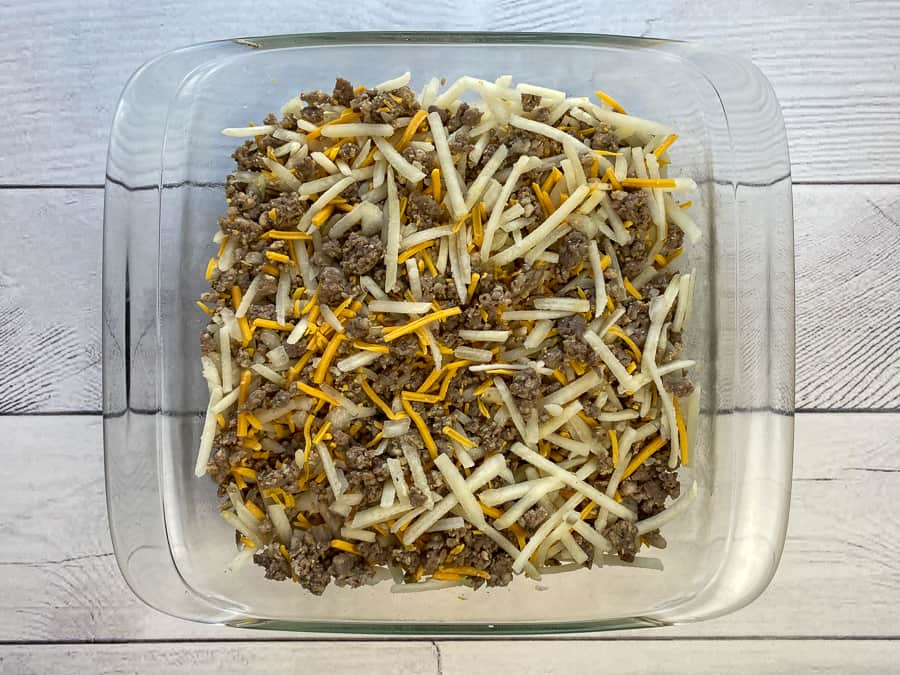 Cooked sausage, onions, hash browns and cheese mixed in 8-inch square dish on white vinyl