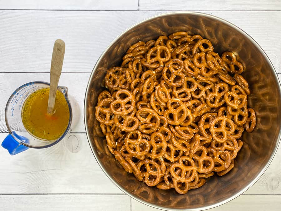 Cup with spiced pretzel mix next to pretzels in a large bowl