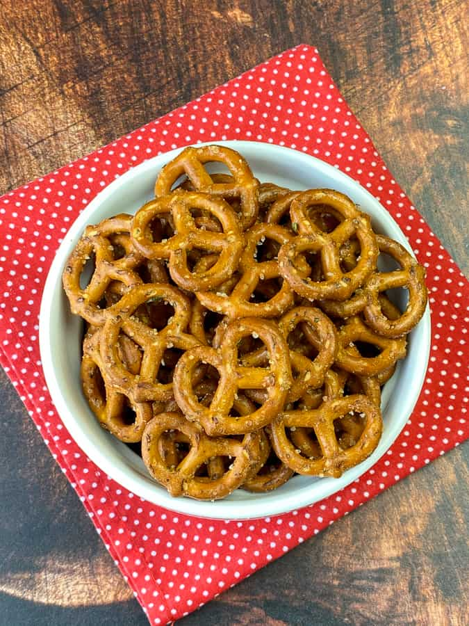 Overhead view of spicy ranch pretzel snack on wooden table with red polka dot napkin