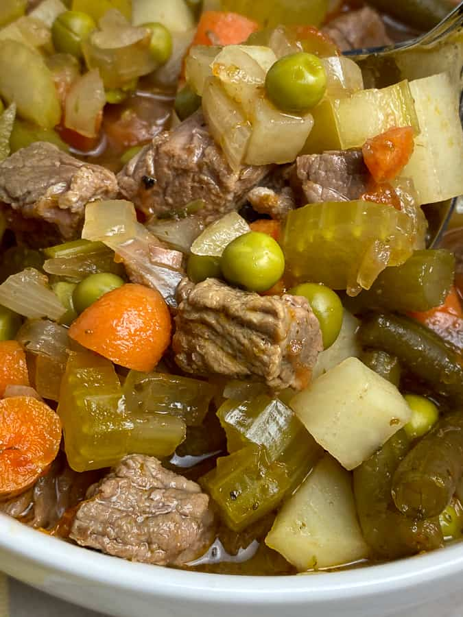 Small bits of top round steak, carrots, celery, onion, peas, potatoes and green beans in soup