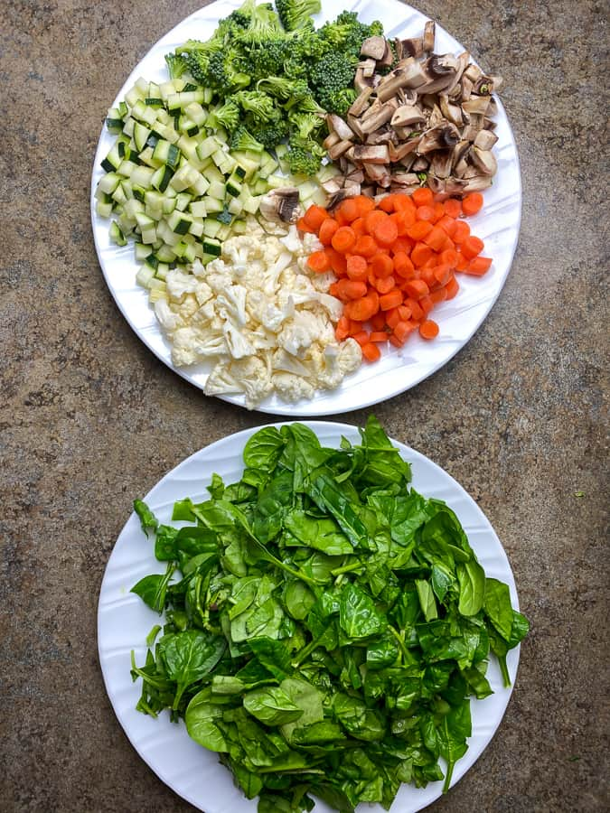 Plates of spinach and chopped vegetables for filling for stuffed shells