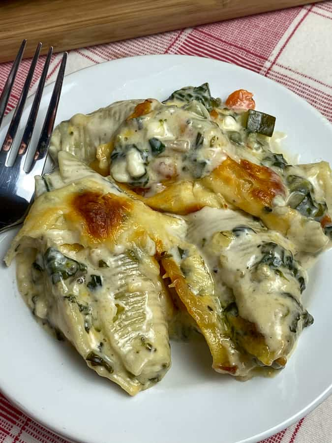 Cheesy large shells stuffed with veggies and covered with alfredo sauce