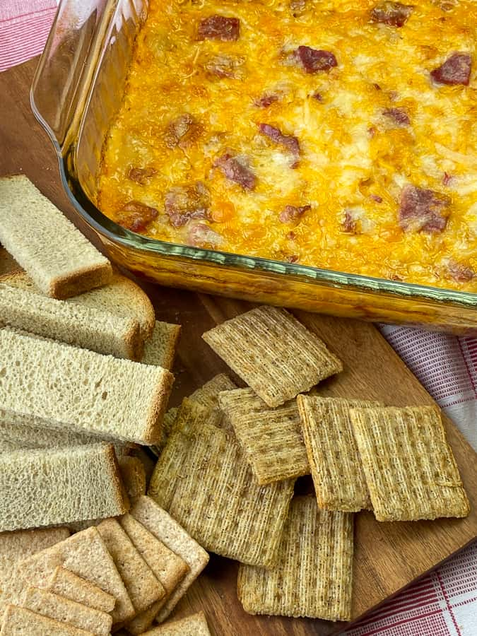 Whole wheat crackers and rye bread next to warm reuben dip