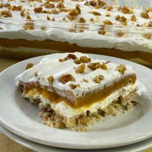 Square piece of butterscotch delight dessert on a white plate