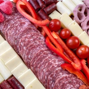 Sliced cheese, salami, red peppers, tomatoes, pretzels and candy on a charcuterie board