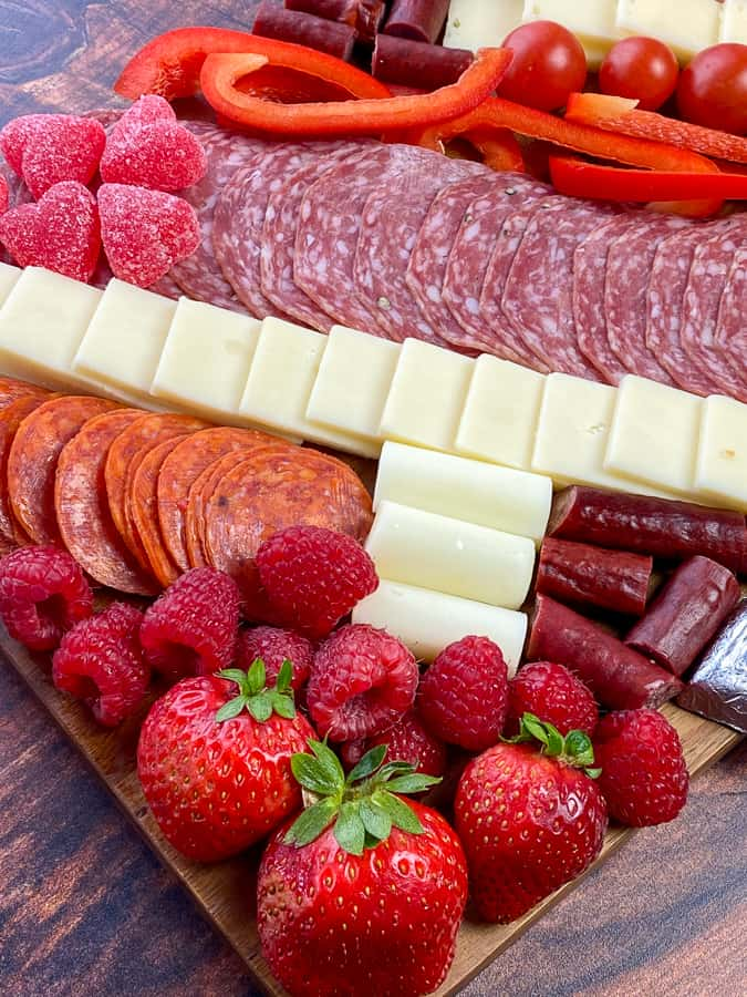 Common fruit, meat, cheese sticks and slices and candy on a cheap charcuterie board