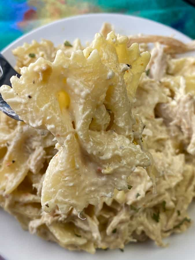 Bowtie pasta on fork covered in cream cheese, chicken, cream of chicken soup and Italian seasoning