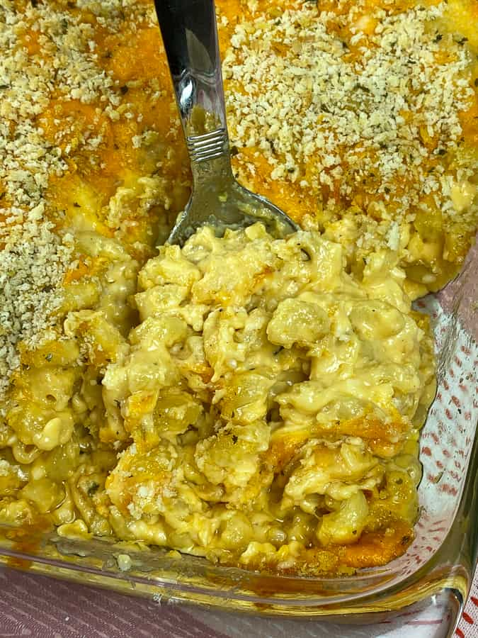 Serving spoon in super cheesy homemade baked macaroni and cheese