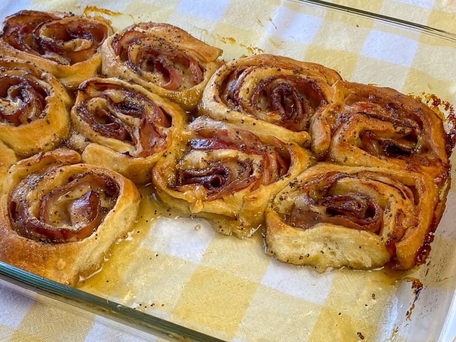 Center of pan showing glazed and baked ham and cheese roll-ups