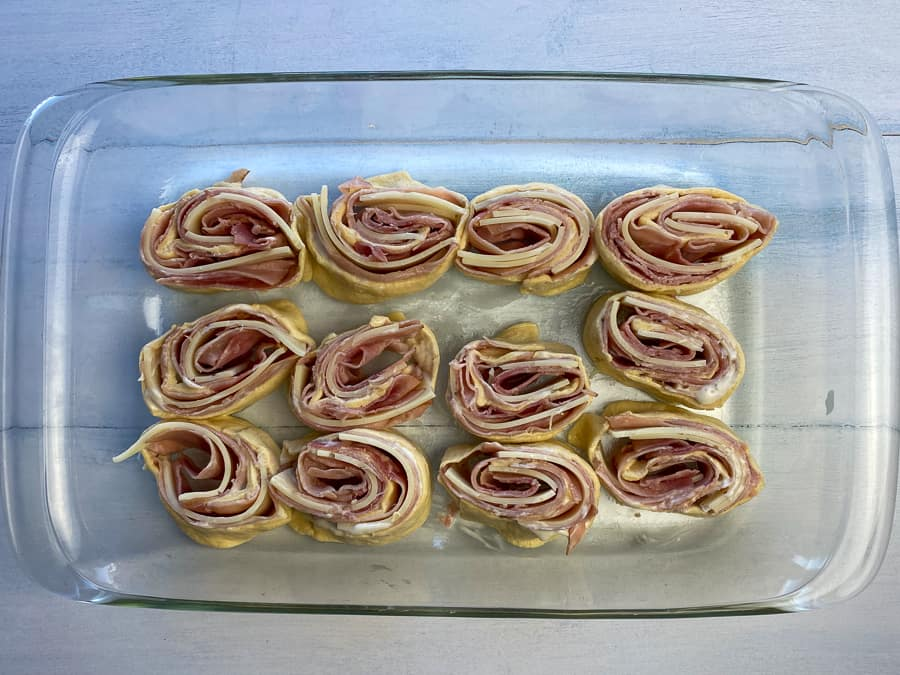 Ham and cheese roll-up slices on their side in a 9 x 13 baking dish