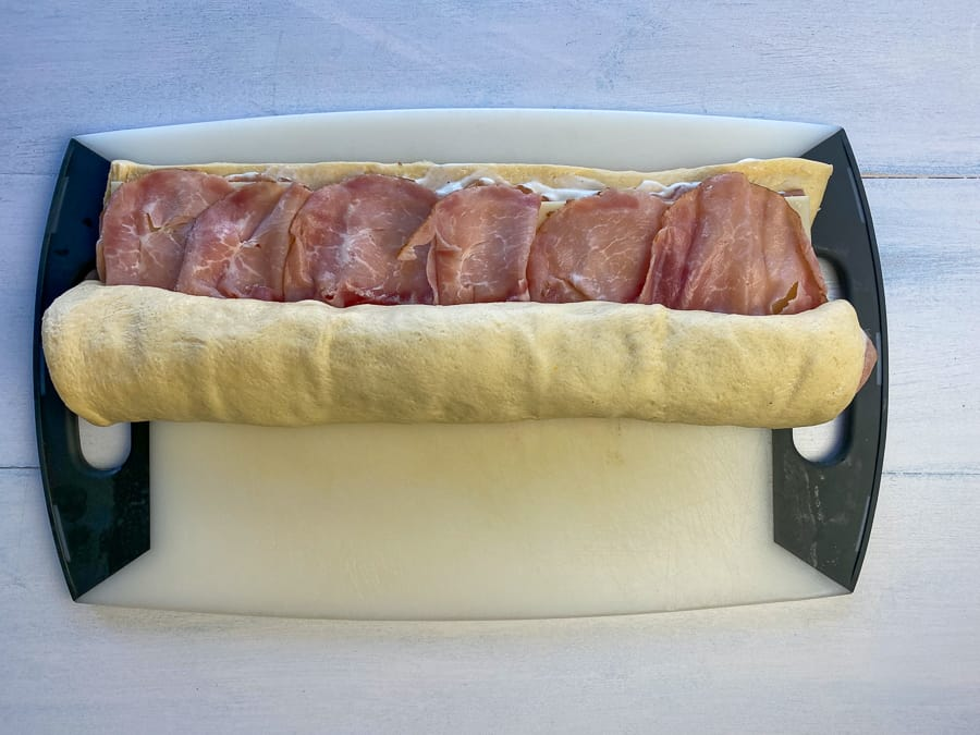 Starting to roll the ham and cheese up in refrigerated dough