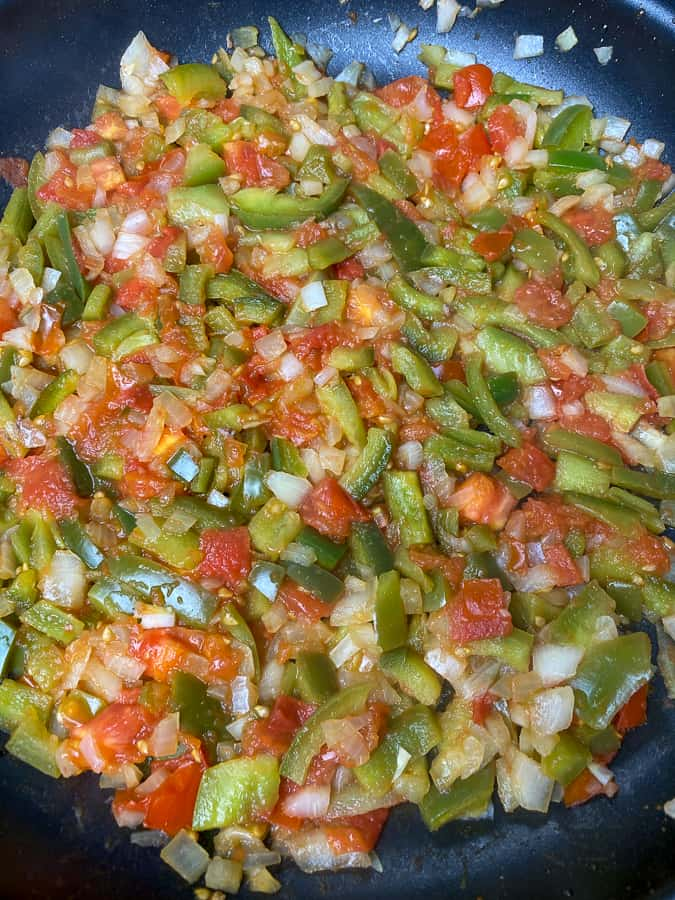 Cooked green peppers, onions and tomatoes in skillet