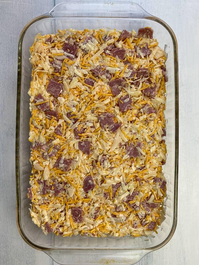 Shredded cheese with corned beef, sauerkraut, dressing, horseradish and mayo mixed up in baking dish