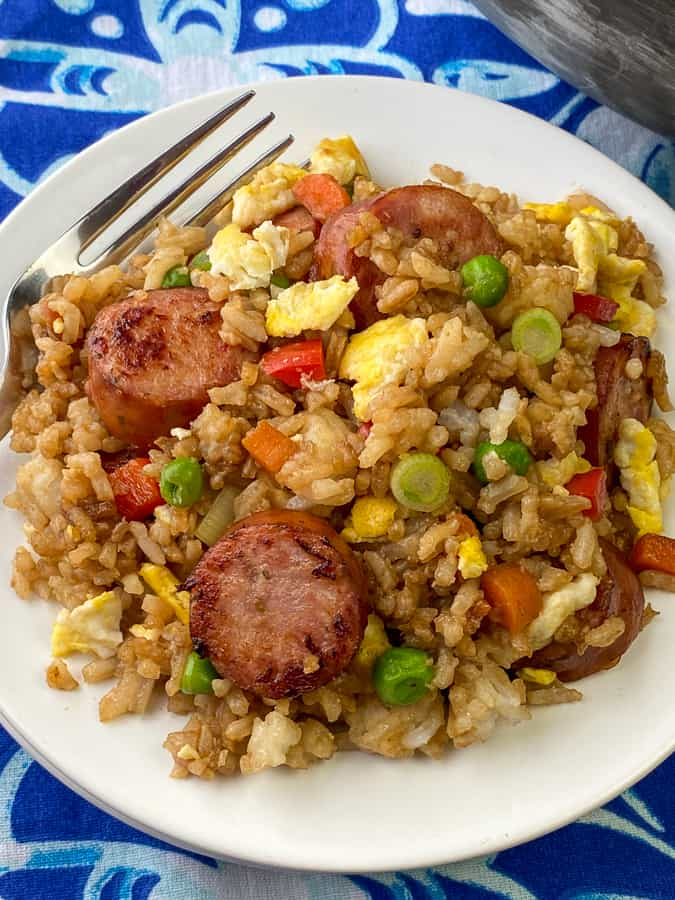 Fork in veggie, sausage and egg fried rice covered in soy sauce